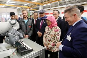 President Halimah Yacob watches a robotic arm in action at the facility of German electrical equipment company ABB Stotz in Heidelberg, Germany, on Dec 12, 2019. She is accompanied by her husband Mr Mohamed Abdullah Alhabshee (on her right), Senior P