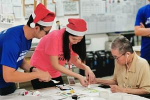 Volunteers Ashley Lee (centre) and Lee Yong Quan (left) prepare festive crafts with a resident of Thye Hua Kwan Nursing Home in Hougang on Dec 14, 2019.