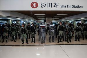 Police officers stand guard at the entrance of Sha Tin MTR station during a protest at the New Town Plaza shopping mall in Hong Kong, on Dec 15, 2019.
