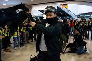 A police officer reacts as an umbrella is thrown towards him during a protest at the New Town Plaza shopping mall in Shatin in Hong Kong on Dec 15, 2019.
