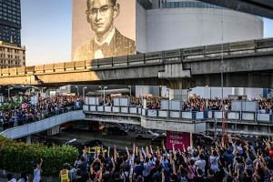 A photo taken on Dec 14, 2019 shows Thai Future Forward Party supporters standing on a skywalk bridge in front of a mural featuring the late Thai King Bhumibol Adulyadej during an unauthorised flash mob rally in Bangkok.