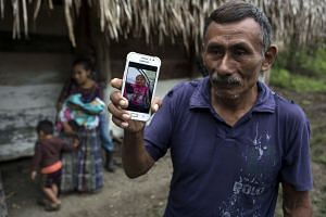 Domingo Caal Chub, 61, holds a smartphone displaying a photo of his granddaughter Jakelin, in Guatemala.