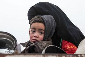 A Syrian boy is held by a woman in the back of a truck as part of a convoy fleeing bombardment in Idlib.