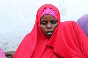 Qali Ibrahim is consoled by an unknown relative during a Reuters interview at the Madina hospital in Mogadishu.