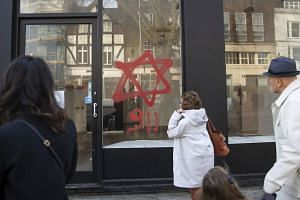People look at anti-Semitic graffiti on a shop window in Belsize Park, North London.