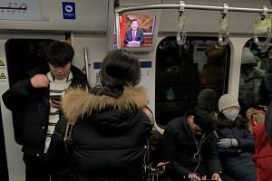 Passengers on a subway train in Beijing, China, are seen next to a screen broadcasting news of Chinese President Xi Jinping's New Year speech.