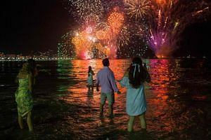 People celebrating as they watch the traditional New Year's fireworks at the Copacabana Beach in Rio de Janeiro, Brazil, on Dec 31, 2019.