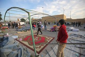 Supporters and members of Iraq's Hashed al-Shaabi paramilitary force dismantle their tents as they prepare to withdraw from the US embassy perimeter in the Iraqi capital Baghdad on Jan 1, 2020.