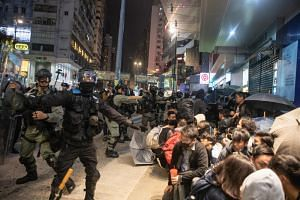 People detained by riot police sit during a protest in the Causeway Bay district of Hong Kong, on Jan 1, 2020.