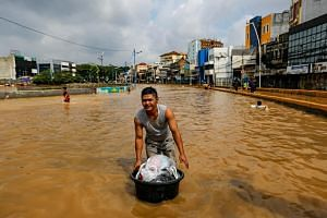 A man floats his belongings across floodwaters at the Jatinegara area after heavy rains in Jakarta, Indonesia, on Jan 2, 2020.