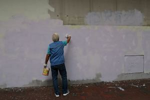 In a picture taken on Dec 9, a man paints over protest graffiti slogans from the previous day's protest march in Hong Kong.