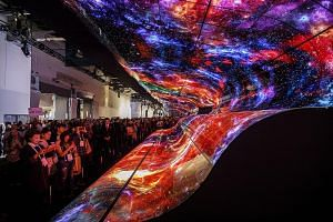 Attendees taking photographs of a curved electronic display wall at the entrance to the LG Electronics booth at last January's CES trade show in Las Vegas. This year's show, starting next week in the same US city, is not expected to feature any break