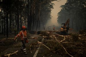 Crews clear debris from a roadway near Jerrawangala, Australia on Jan. 2, 2020.