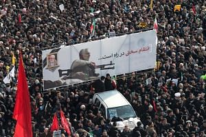 Iranian mourners carry a banner as they gather to pay tribute for Qassem Soleimani's funeral in Teheran, Iran, on Jan 6, 2020.