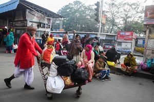 People wait for transportation outside the Howrah railway station during a nationwide general strike to protest the Indian government's economic policies, in Kolkata, on Jan 8, 2020.