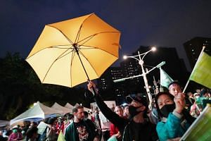 A man from Hong Kong holds a yellow umbrella at a rally for Taiwanese President Tsai Ing-wen in Taipei, on Jan 10, 2020.