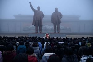 People preparing to bow as they pay their respects before a statue of late North Korean leaders Kim Il Sung (left) and Kim Jong Il on Mansu Hill in Pyongyang, on Dec 17, 2019.