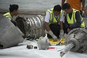 A photo taken on Nov 7, 2018, showing investigators examining engine parts from the Lion Air flight JT 610 that plunged into the Java Sea.