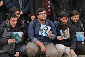 Iranian students hold pictures of victims during a memorial for the passengers of the Ukraine plane crash, at the University of Teheran on Jan 14, 2020.