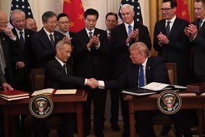 US President Donald Trump (right) and China's Vice-Premier Liu He (left) shake hands as they sign the trade deal.