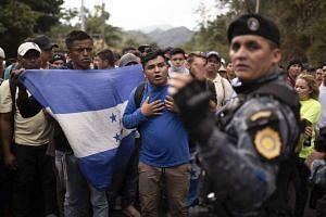 Honduran migrants walking in a group stop before Guatemalan police near Agua Caliente, Guatemala.