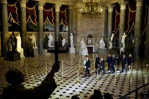 The House impeachment managers pass through Statuary Hall as they take the articles of impeachment from the House to the Senate chamber at the Capitol in Washington on Jan 15, 2020.