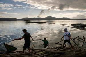 A group of fishermen make repairs to their operations affected by the ashfall from the eruption of the Taal volcano, in Buso Buso on Jan 20, 2020.