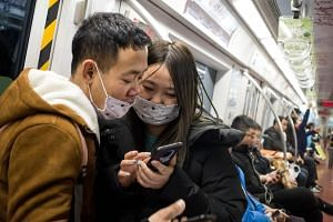 Subway passengers wear protective masks in Beijing, on Jan 21, 2020.