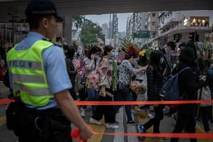 Shoppers wearing surgical masks are directed by a police officer at a flower market in the Mong Kok district of Hong Kong, on Jan 24, 2020.
