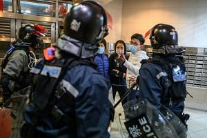 People argue with riot police inside the lobby of a residential building as residents protest against plans for an empty local housing estate to become a temporary quarantine camp in the Fanling district in Hong Kong on Jan 26, 2020.