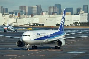 A charter flight from the Chinese city of Wuhan, which was arranged by Japan's government to evacuate its citizens, lands at Haneda airport in Tokyo on Jan 29, 2020.