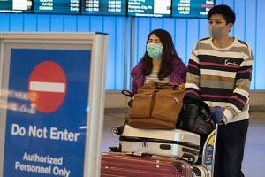 Passengers in protective masks arriving at the Los Angeles International Airport in California, on Jan 25, 2020.