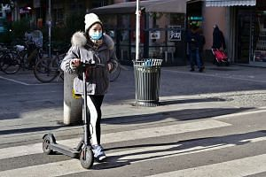 A woman wearing a mask walks by her electric scooter in via Paolo Sarpi, the commercial street of the chinese district of Milan on Jan 30, 2020.