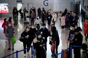 Passengers wearing masks are seen at the Pudong International Airport in Shanghai on Jan 27, 2020. An informal grouping of Hubei natives managed to send the items to China via Shanghai's Pudong airport.