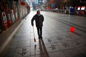 A man wearing a face mask as he practises Chinese calligraphy on a pavement in Jiujiang, Jiangxi province, on Feb 3, 2020.