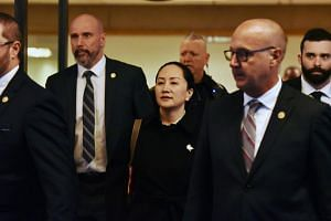Huawei chief financial officer Meng Wanzhou (centre) leaves British Columbia Supreme Court with her security detail in Vancouver, Canada, on January 23, 2020.