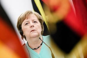 Merkel listens at a joint press conference in Angola with President Joao Lourenco on Feb 7, 2020.