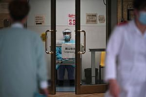 A medical worker in protective gear waiting to take the temperature of visitors at the Princess Margaret Hospital in Hong Kong on Feb 4, 2020.