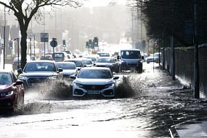 Cars drive through floodwater as hurricane-force winds and rain affected the country's transport network leading to disruptions and prompting warnings of power cuts and a risk to life, in Manchester, Britain, on Feb 9, 2020.