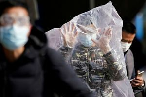 A commuter wearing a mask and covering himself with a plastic bag outside Shanghai railway station on Feb 9, 2020.