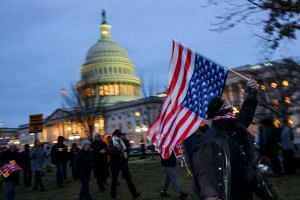 A protester waves a US national flag upside down, in a sign of distress, outside the Capitol in Washington, DC, on Feb 5, 2020.
