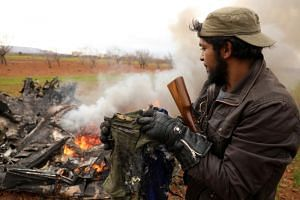 A man inspects the belongings of a pilot who was on an alleged Syrian army helicopter that was shot down in the village of Qaminas, east of Idlib, Syria, on Feb 11, 2020.
