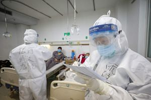 Two medical personnel work in the patients' ward in Jinyintan Hospital in Wuhan, Hubei province, China, on Feb 13, 2020.
