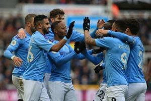 Manchester City's Raheem Sterling (third left) celebrates scoring a goal with team mates.