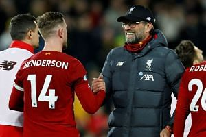 Liverpool manager Juergen Klopp celebrates with Jordan Henderson after the match.