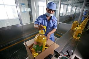 In a photo from July 4, 2018, a worker packs bottles of soybean oil made from imported US soybeans at Liangyou Industry and Trade Co., Ltd in Qufu, Shandong province.