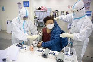 Medical staff in protective suits attend to patients at Wuhan Fang Cang makeshift hospital in Wuhan, Hubei province.