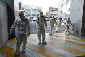 South Korean health officials wearing protective suit and spraying disinfectant in front of the Daegu branch of the Shincheonji Church of Jesus in South Korea, on Feb 19, 2020.