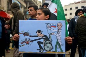 A young Syrian holds a caricature representing Syrian President Bashar al-Assad and Russian President Vladimir Putin as he takes part in a demonstration to protest against the continuing assault by the Syrian regime and Russian forces on the last reb