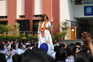 """Sporting a traditional red """"tilak"""" dot on her forehead and wearing a garland of marigolds, US First Lady Melania Trump watched children at the school play, do yoga, and perform a bhangra dance."""